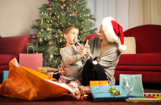 Мать и сын играют вместе с елочными игрушками