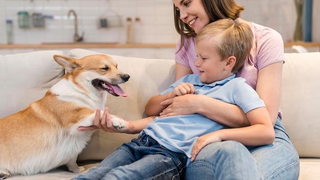 Мать и сын играют с собакой корги