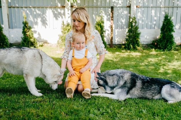 庭で2匹の犬とポーズをとる母と息子