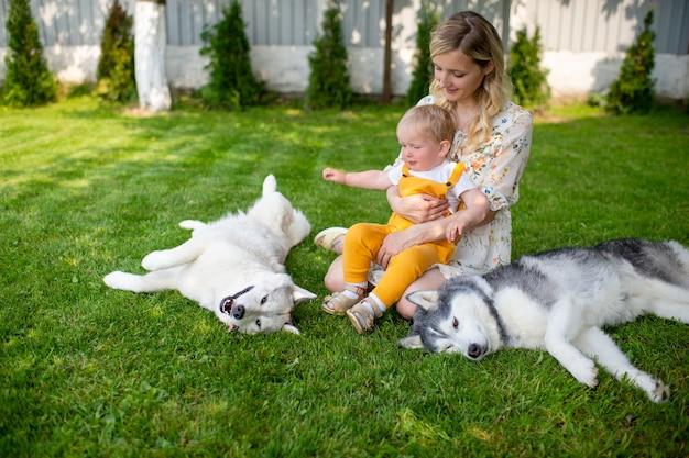 草の上で2匹の犬とポーズをとる母と息子
