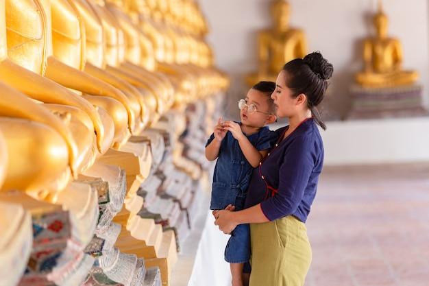 Мать и сын молятся статуе будды уважения в храме ват пхуттай саван, аюттхая, таиланд. концепция тайской культуры
