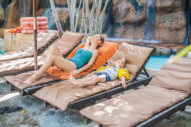수영장 옆 일광욕에 편안한 어머니와 아들