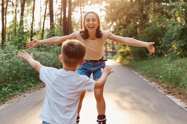 여름 공원에서 어머니와 아들 롤러 스케이트, 엄마에게 흰색 티셔츠를 타고 어린 소년의 다시보기, 긍정적 인 표정으로 그녀의 아이를 잡는 행복한 여성, 롤러 블레이드.
