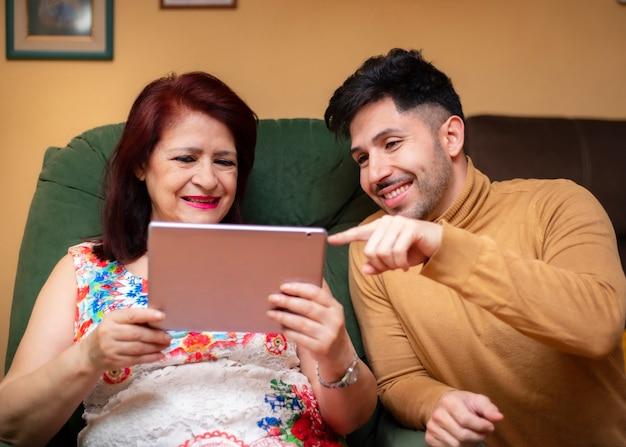Мать и сын, покупки в интернете. семейные поколения, использующие технологии планшетных компьютеров