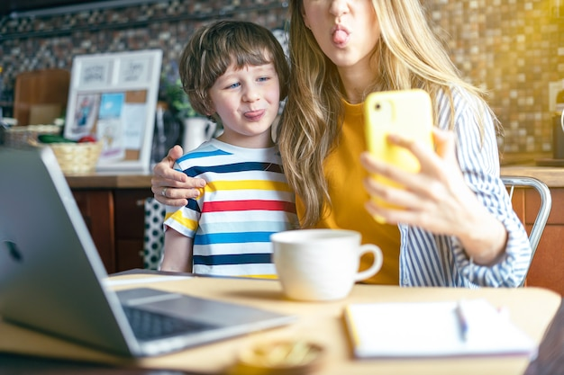 Мать и сын показывают язык, делают селфи, глядя на смартфон, веселятся вместе дома женщина