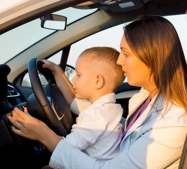 Мать и сын сидят за рулем автомобиля с руками ребенка за руль, как будто за рулем