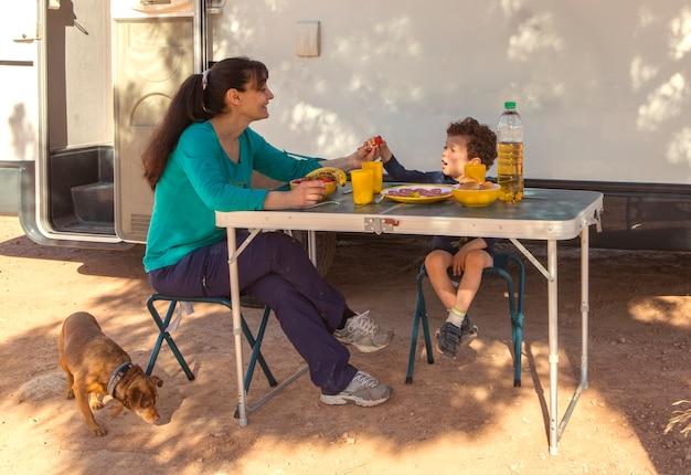 木陰でピクニックをしているキャラバンの前に座っている母と息子