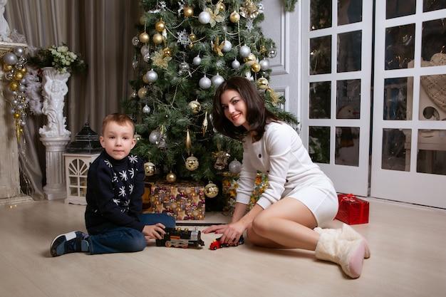 母と息子のクリスマスツリーのそばに座って