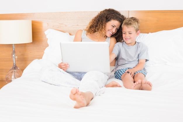 어머니와 아들이 노트북을 사용하여 침대에 앉아