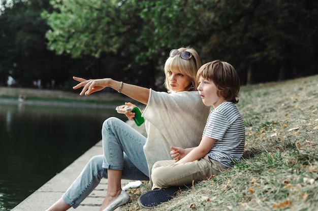 Мать и сын, сидя на берегу реки в парке, ребенок и его мама отдыхают на берегу пруда в