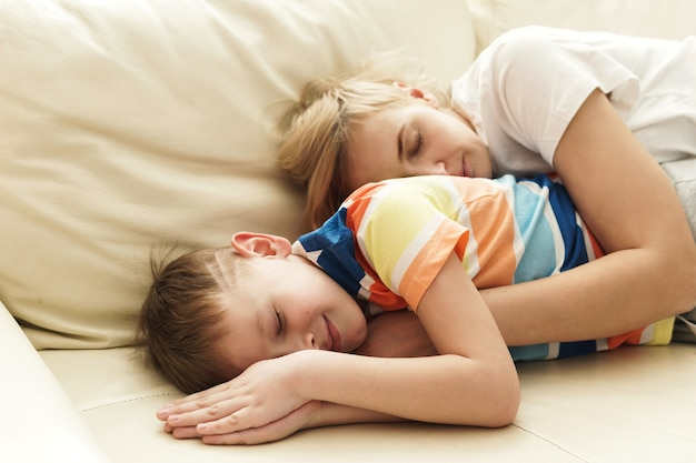 Мать и сын спят на диване после активных игр
