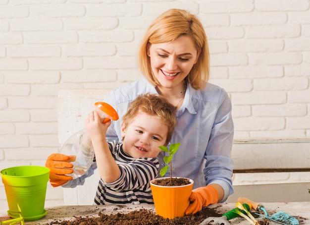 母と息子が植木鉢に花をスプレーします。家族関係。自宅でのガーデニング。植物の世話。