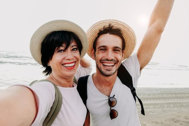 母と息子がスマートフォンでビーチでselfieを取っています。