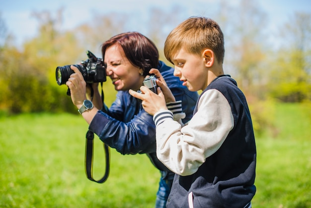 Мать и сын фотографируют на открытом воздухе