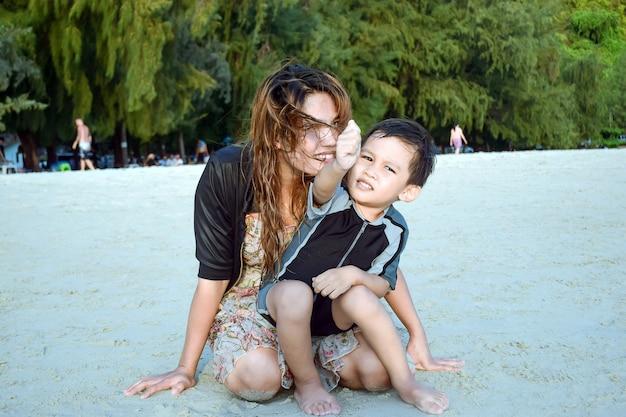 週末にビーチでふざけてからかう母と息子