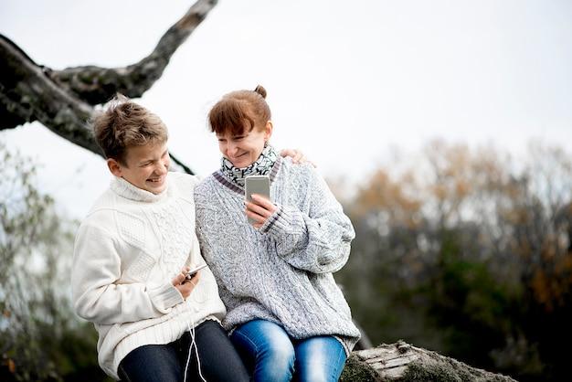 어머니와 아들 십대는 나뭇 가지에 등을 대고 앉아 휴대 전화와 헤드셋을 사용합니다.