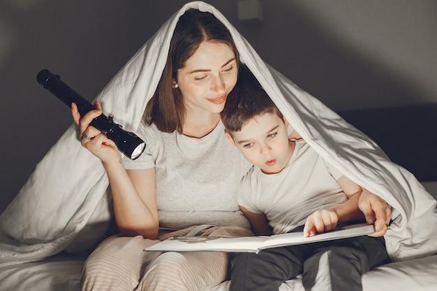 Мать и сын под одеялом в постели читают книгу.