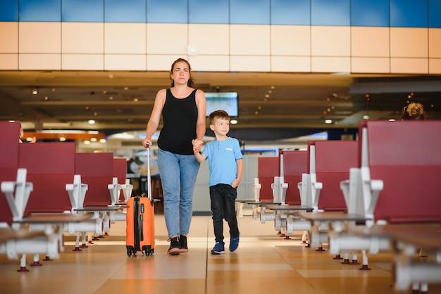 Мать и сын ждут посадки у выхода на посадку современного международного терминала.