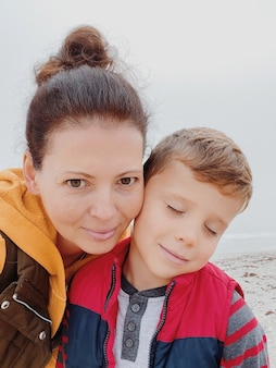Мать и сын гуляют по туманному пляжу и делают селфи по телефону. портрет счастливой мамы и малыша мальчика пасмурной погоды с телефоном. семейное время вместе.