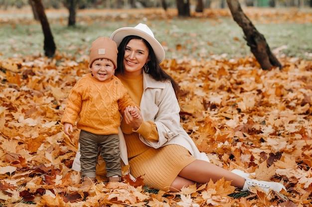 母と息子が秋の公園を歩く