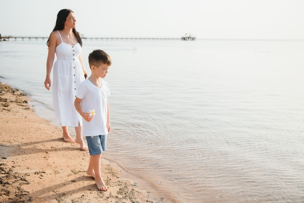 Мать и сын гуляют по пляжу