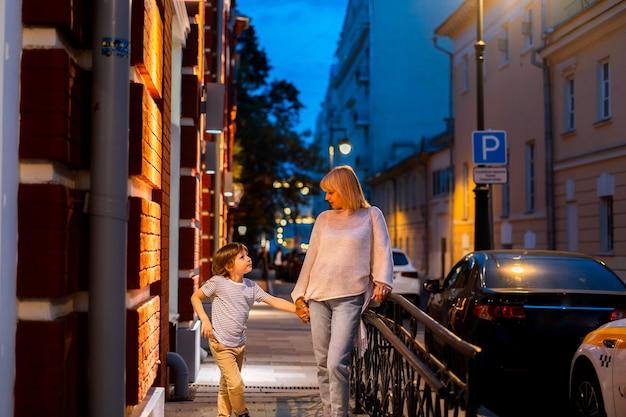 Мать и сын гуляют по улице в центре города мама и ребенок гуляют летним вечером на улице