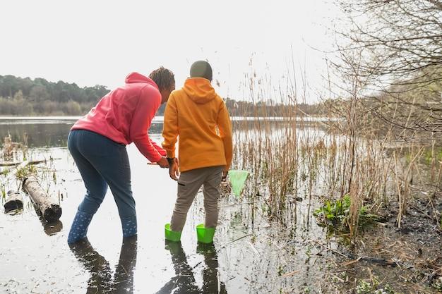 泥だらけの場所を歩く母と息子