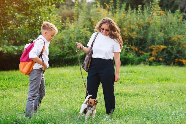 어머니와 아들이 공원에서 자신의 강아지와 함께 산책. 작은 강아지 잭 러셀 테리어와 아이 야외. 행복, 우정, 동물 및 생활 양식. 행복한 가족.
