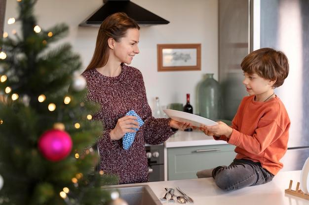 クリスマスの日に一緒に皿を洗う母と息子