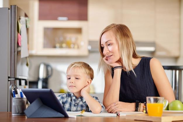 Мать и сын смотрят веб-семинар или онлайн-класс на планшетном компьютере, сидя за кухонным столом дома