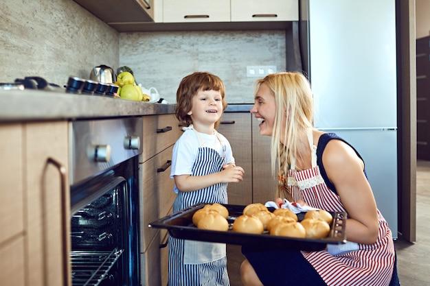 어머니와 아들이 부엌에서 오븐에서 잎의 쟁반과 함께.