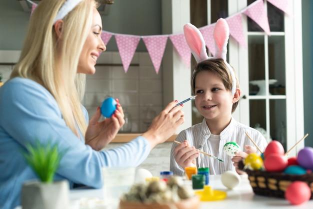 토끼 귀 머리띠와 집에서 부활절 달걀을 그린 어머니와 아들