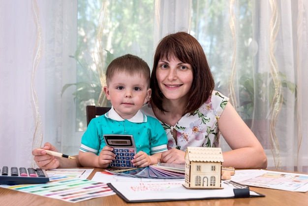 家のモデルとペイントツールを持つ母と息子