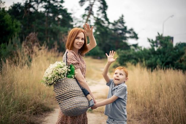 Мать и сын с рыжими волосами с большим букетом полевых цветов на природе летом