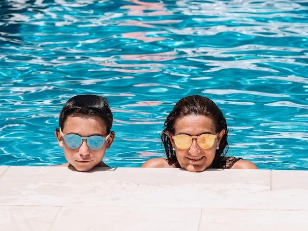 Мать и сын в солнечных очках, опираясь на край бассейна в солнечный летний день