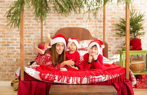 Мать и сыновья в рождественской пижаме сидят на кровати и радуются