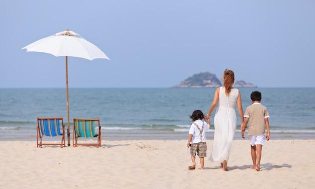 Мать и сыновья гуляют по пляжу Premium Фотографии