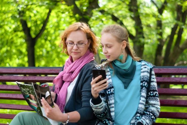 母と十代の娘は、いくつかの雑誌の紙とモバイル電子版を読んでいます