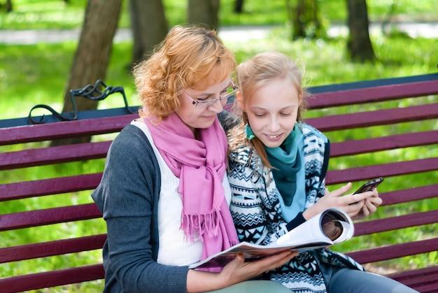 엄마와 십대 딸이 종이와 모바일 전자 버전의 잡지를 읽고 있다