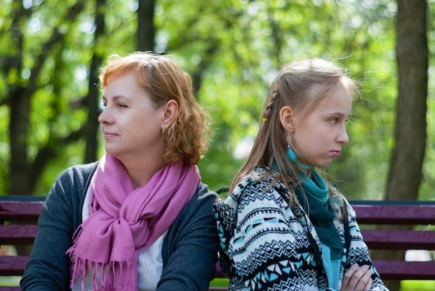 母と十代の娘は、お互いに背を向けて閉じたポーズで公園のベンチに座っています
