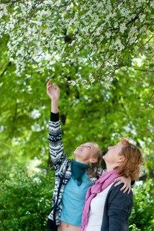 어머니와 십대 딸은 공원에서 꽃이 만발한 사과 나무를 의사 소통하고 존경합니다