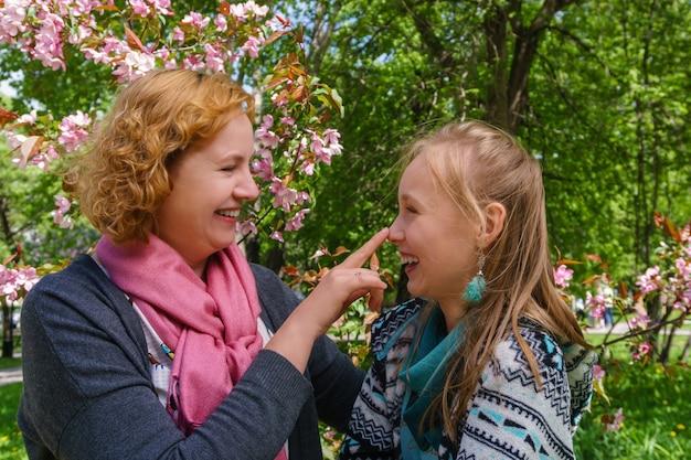 어머니와 십 대 딸이 서로 이야기 하는 약간의 농담 웃으면서 공원에서 재미