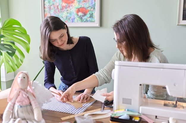 Мать и дочь-подросток шьют вместе дома. мама учит дочку шить на машинке, женщины шьют игрушку и одежду для игрушки. родитель и подросток, отношения, образ жизни, творчество, навыки