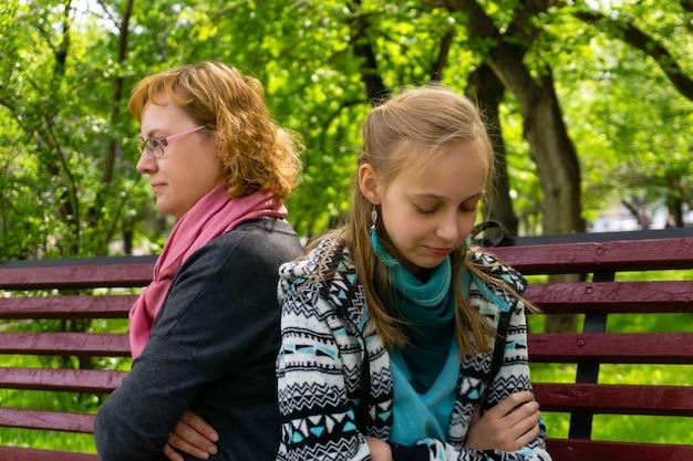 母と十代の娘は、閉じたポーズでお互いに背中を向けて公園のベンチに座っています