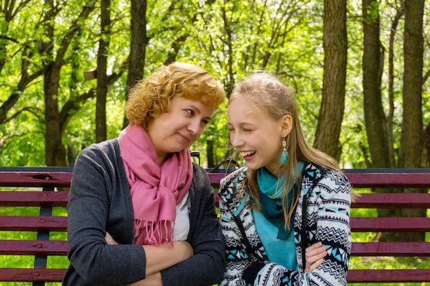 母と十代の娘が公園のベンチで何か