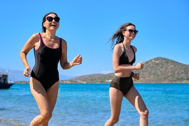 엄마와 십대 딸이 함께 해변에서 수영복을 입고 바다로 달리고 있습니다. 가족 휴가, 우정과 부모와 십대 간의 의사 소통. 여름 방학, 바다, 라이프 스타일, 레저, 가족