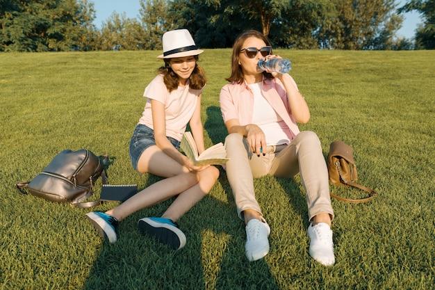 Мама и девушка гуляют в летнем парке, пьют напитки, отдыхают на траве