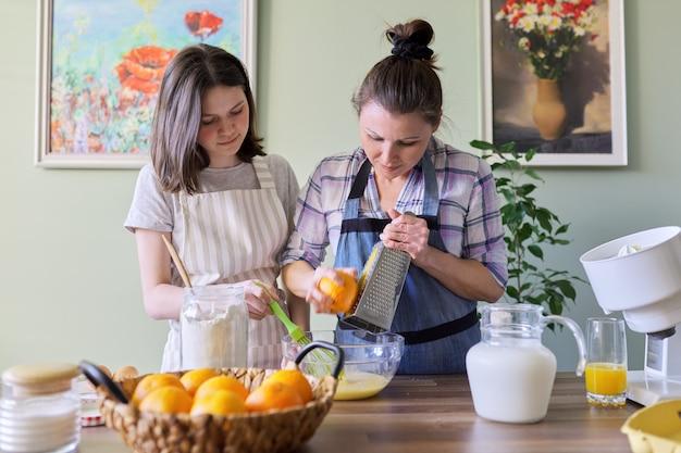 어머니와 10대 딸은 집에서 오렌지 향과 주스를 곁들인 팬케이크를 함께 요리합니다. 가족, 취미, 라이프스타일, 집에서 만든 맛있고 건강한 음식