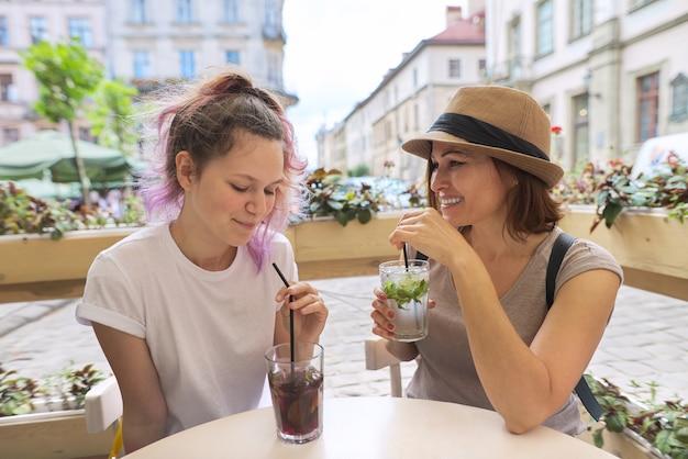 街の屋外カフェに座って話している母と10代の娘