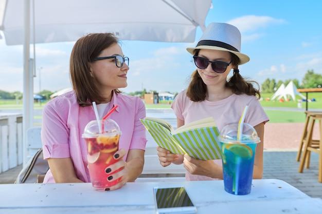 Мать и дочь-подросток вместе в летнем летнем кафе с безалкогольными напитками, читая книгу, блокнот